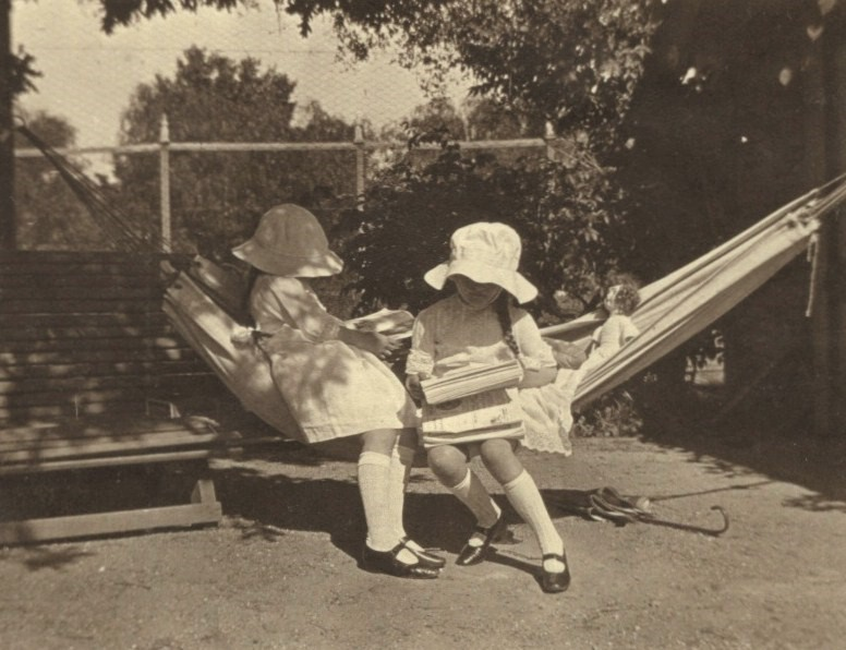 Two grandchildren reading on the hammock