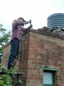 Glenn from Philipson Masonry repointing the parapet brickwork on the toilets